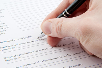 Hand filling in medical questionnaire form in a clipboard