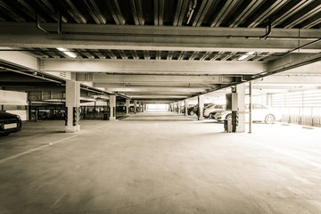 Parking garage, interior with a few parked cars.
