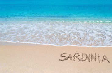 """turquoise foreshore with """"Sardinia"""" written on it"""
