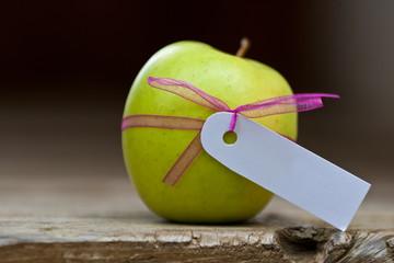 grüner Apfel mit Schleife und weißem Schild
