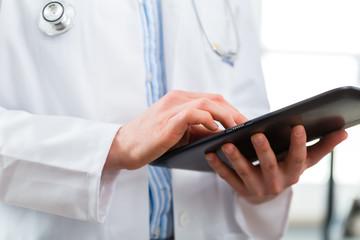 Arzt in Praxis liest eine digitale Krankenakte