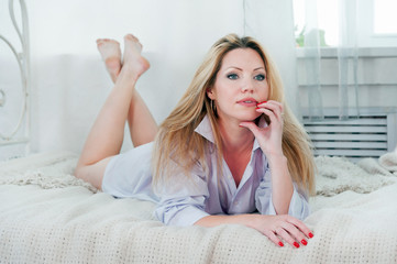 Pretty woman thinks while lying on the bed