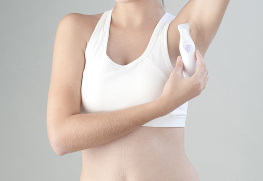 Woman trimming her armpit with electric trimmer