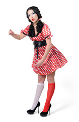 Pinup girl in a red and white polka-dot dress on white