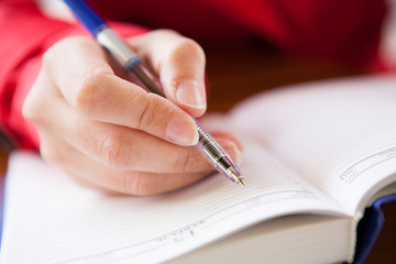 Fototapete - Close-up of hand writing in diary