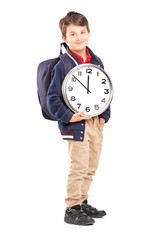Full length portrait of a school boy with backpack holding a clo