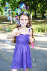 Cute  girl blowing soap bubbles outdoors