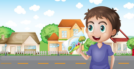 A boy holding a picture in front of the houses near the road
