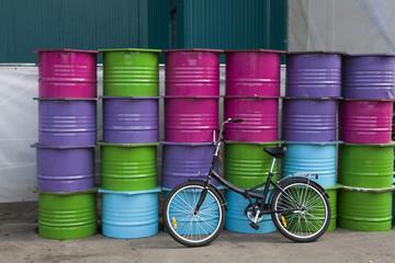 Bicycle near plenty of colour barrels