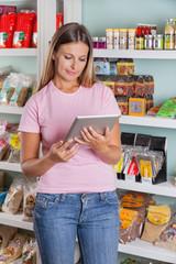 Woman Using Digital Tablet In Supermarket