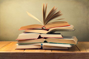 Open old books on wooden table over grunge background