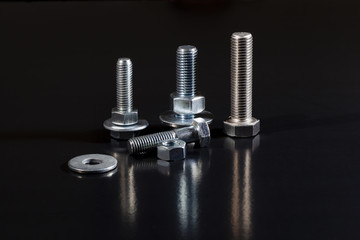 Bolt screws, nuts and washers on reflective black background
