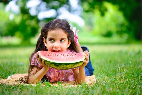 Cute hispanic girl eating watermelon