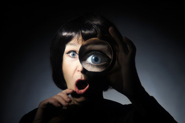 Woman with magnifying glass surprised