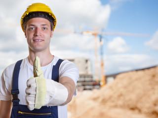 Bauarbeiter zeigt Daumen vor Baustelle mit Erdarbeiten