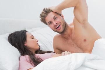 Shirtless man posing next to his sleeping partner