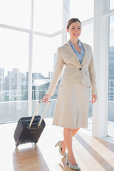 Businesswoman pulling her suitcase and smiling at camera