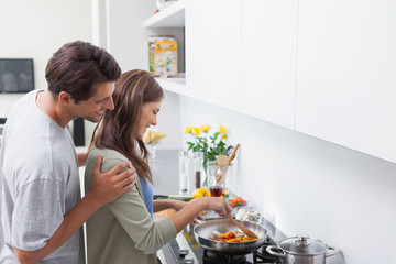 Man looking at his wife cooking