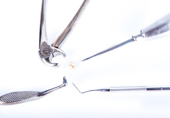 Dental tools around real extracted tooth, with caries
