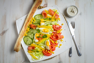 Salmon salad with tomato, eggs and cucumber