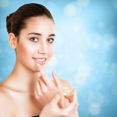 attraktive brünette junge Frau trägt Lipgloss auf