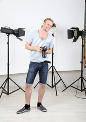 Handsome photographer with camera at working,