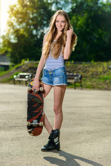 Beautiful happy woman holding her skateboard outdoors
