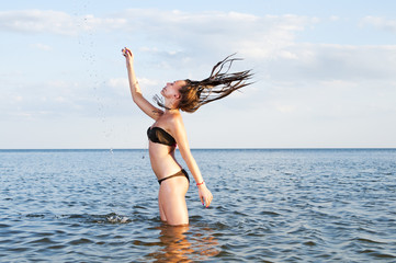Young woman stands in water splashes