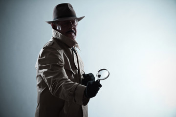 Silhouette of detective with mustache and hat. Holding magnifyin