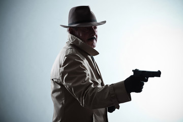 Silhouette of detective with mustache and hat. Holding gun. Stud