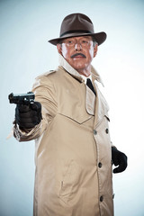 Vintage detective with mustache and hat. Holding gun. Studio sho