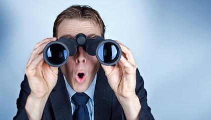 Businessman looking through field glasses or binoculars