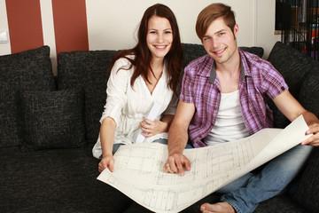 Glückliches junges Paar mit Bauplan - couple construction plan