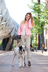 Female walking her dog outdoors and talking on mobile phone