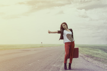 girl standing on road with suitcase looks for fellow traveler