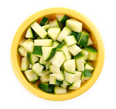 Chopped zucchini in a bowl isolated on white