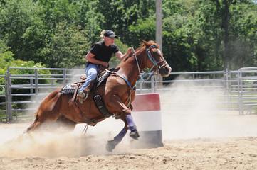 Young adult woman barrel racing