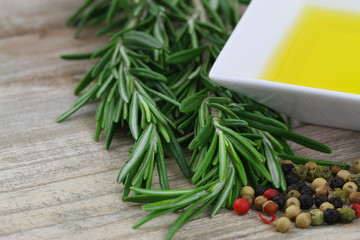 Rosemary, mixed peppers and olive oil on wooden background