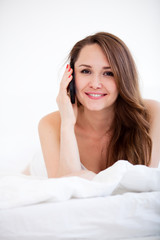 woman with phone lying on bed