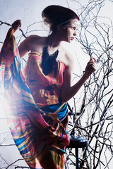 beautiful woman in a dress fashion in the branches of trees
