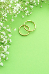 Wedding invite with rings, flowers and green background