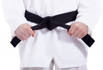 Fotorollo Kampfsport Martial arts man tying his black belt, isolated on white