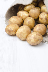 new potatoes in a sack on white wooden board and space for text