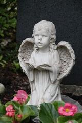 Betender Engel auf einem Grab mit Blumen