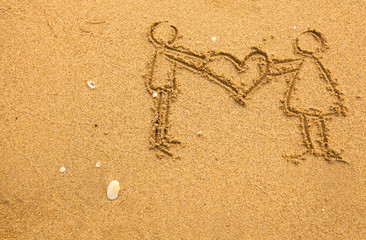 In texture of sand: a pair holding a big heart.