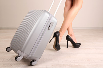 Girl's legs with suitcase in room