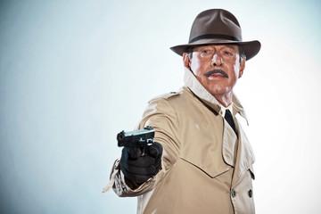Retro detective with mustache and hat. Holding gun. Studio shot.