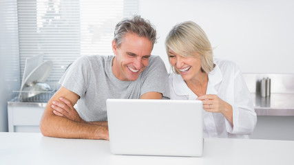 Happy couple laughing at laptop in the morning