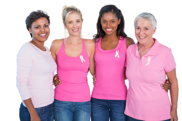 Smiling women wearing pink tops and breast cancer ribbons