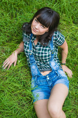 Portrait of pretty brunette lying on grass